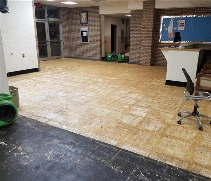 Front lobby with drying equipment and removed floor panels due to damage