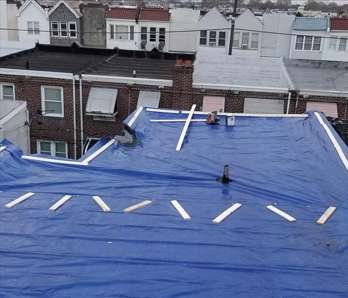 SERVPRO remediating the roof with tarps to prevent further leaks