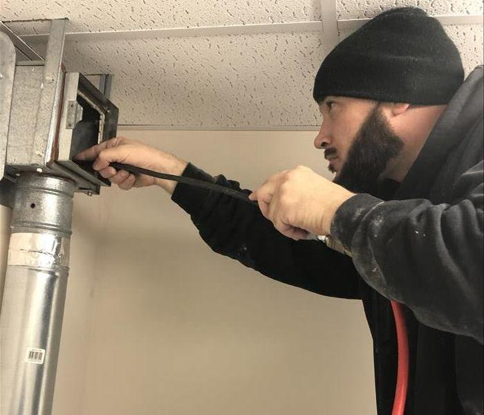 SERVPRO technician cleaning the air duct